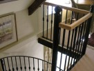 Wooden Spiral Staircase with metal balusters and metal handrail to spiral
